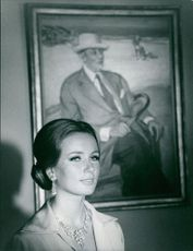 Geneviève Gilles standing in front of a man portrait.