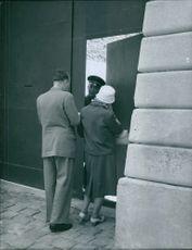 Man and woman inquiring at the gate. 1960