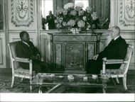 First President of Côte d'Ivoire Félix Houphouët-Boigny seen with former French President Charles de Gaulle, they are sitting and having a conversation