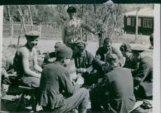 Soldiers sitting and chopping the vegetables.