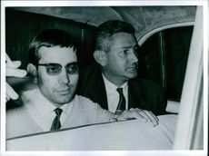 Two men sitting at the back seat, the other man is pictured smoking a cigarette.