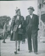 Maurice Chevalier walking with woman and facing each other.