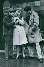 Men standing and looking at puppy, held by a woman.