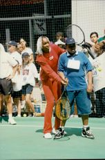 Venus Williams shows some American youth how to play tennis outside the All Star clinic.