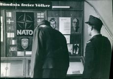 A vintage photo of a German soldier reading publications exhibited about NATO facts and information.