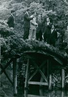 People standing together on the bridge and having discussion.
