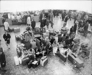 Passengers at London Airport in anticipation of flight delayed by the weather