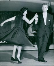 Woman dancing with a man, other people looking at them.