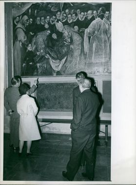 """Gerhard Schröder during his visit of Toledo, points out a detail of Greco's """"The Funeral of Count Orgaz"""" to Mrs. Schröder along with two men. April 5, 1966."""