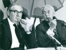 Leonard James Callaghan and Harold Wilson smoking a pipe at press conference. 1974.