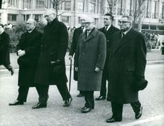 Rene Coty walking with men.
