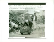The 1994 Northridge earthquake USA:fred rassesy left pushes a tool box from a destroyed.