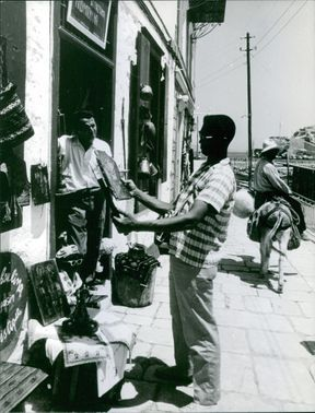 Man looking at roadside items. 1966