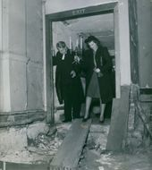 A woman carrying a candle with a man beside her, walking out of the exit door of a damaged building.