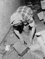 A man trying to salvage books and documents covered with mud in Florence, Italy.  - 1966