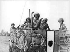 Soldiers pose happily while riding a military truck.