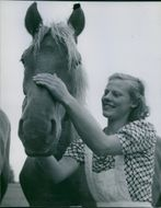 Woman smiling while pampering the horse, 1946.