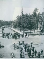 The flag being raised over the U.S Headquarters in Berlin. Watched by President Truman, and a group of Generals, including Gen Eisenhower, Gen Patton, Gen. Bradley and Gen. Vaughan.