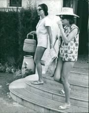 Princess Soraya of Iran  holding bag and going outside with another women.