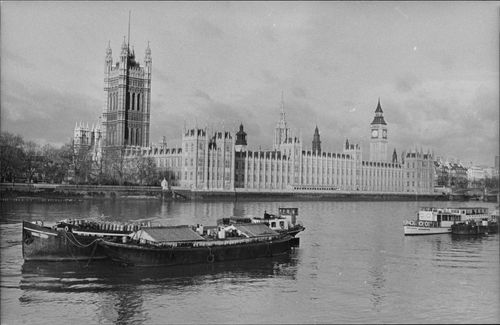 Photography in black and white at the English Parliament Westminster and Big Ben. Boats and the River Thames in the foreground.
