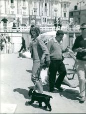 Sylvia Casablancas walking with dog, at Cannes Film Festival 1961.