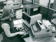 Mrs. Carol Cook, aged 30 and secretary at P.C.D. electronics manufacturers, where the prototype keyboard was made, demonstrating the new keyboard in front of the standard typewriter, 1977.