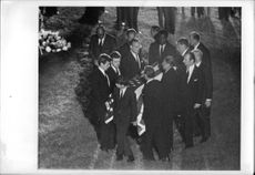 """Robert Francis """"Bobby"""" Kennedy holding flag, with people."""