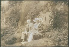 Men and woman siting together beside a cliff. 1918
