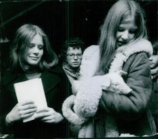 A girl holding an animal in her hands, and another woman standing beside her looking at her and smiling.