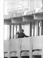 Two men standing in the balcony of a building.