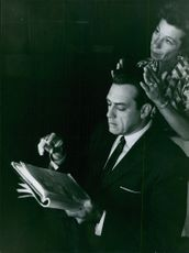 A stylist is fixing Raymund Burr's hair.