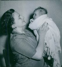 Woman siting and holding a baby.