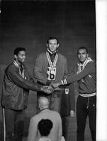 Olympic winners holding hands and wearing their medals.  - 1964