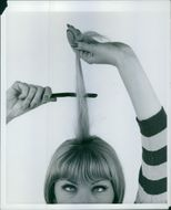 Woman grooming, combing hair for Woman's Realm magazine. 1962.