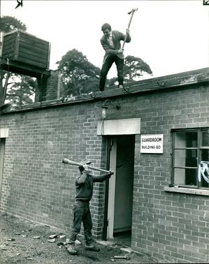 A worker starting to knock down guardroom during the demolition.