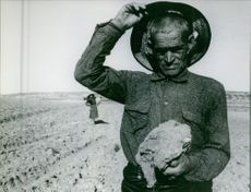 A farmer standing in the field holding piece of sand.
