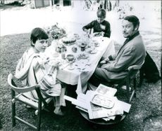 George VI  enjoying breakfast outdoor with his child.