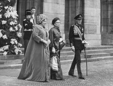 Queen Juliana, husband Prince Bernhard walking with a woman.
