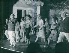 Tino Rossi singing on stage with dancers behind him. 1963.