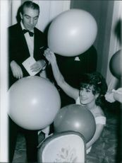 Italian actress Silvana Pampanini holding some balloons.