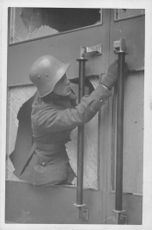 A soldier repairing door, which has been damaged by the explotion of a Russian Aerial bomb nearby, 1940.