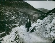 Soldier riding a horse in the rocky road during World War I, 1918.