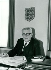 Sir Harold Warris Thompson at his desk in his office.
