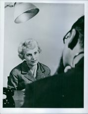 Woman sitting and talking to a man sitting next to him.