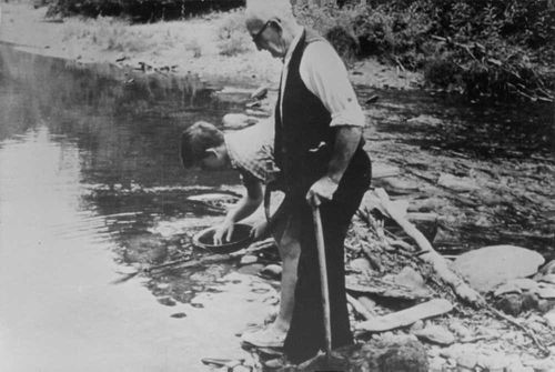 A man holding a dish and doing something near the river, and standing next to him is an old man, 1968.