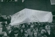 People with banner at baptism ofson of Princess Margriet of the Netherlands and Pieter van Vollenhoven, 1970.