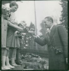 Children giving flowers to Maurice Auguste Chevalier.