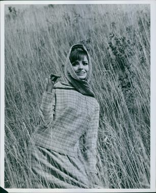 A photo of a woman standing in the field biting a grass.
