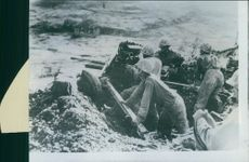 On a slope of a hill on Okinawa A Marine gun crew placed its 37 mm weapon for fire.