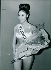 Miss France in her swim suit, holding a bouquet of flowers during a beauty contest.  Taken - Jan 1964